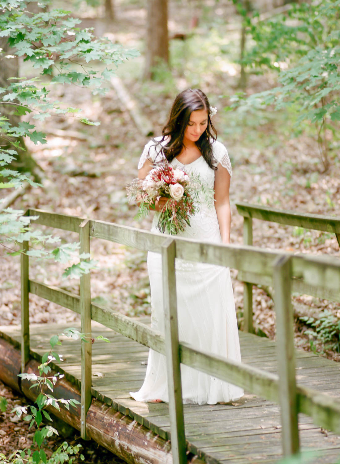 bride in woods on bridge in beaded gown and holding rustic red bouquet, Erica Robnett Photography