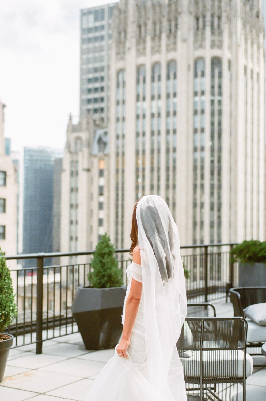 Bride at Gwen Hotel with Chicago skyline, Chicago fine art wedding photographer