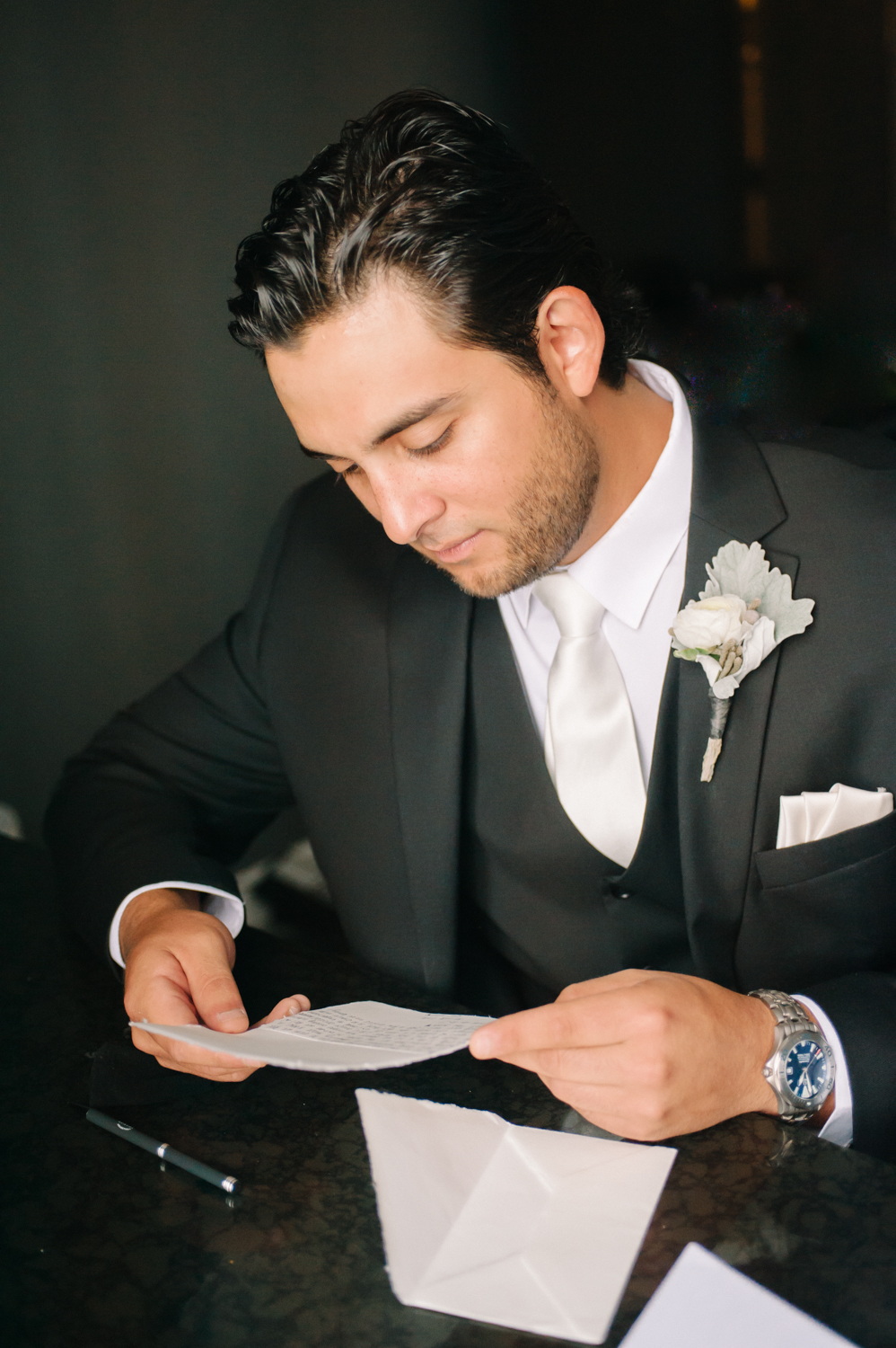 Groom reading letter from bride, St. Louis wedding photographer